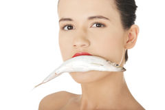 Beautiful woman with fish in her mouth Royalty Free Stock Images