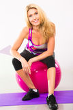 Beautiful woman fitness instructor sitting on stability ball Stock Photography