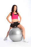 Beautiful woman fitness routine using gym ball. Stretching exercise for beautiful young woman using silver fitness ball during routine. Woman has a happy smile Royalty Free Stock Photo