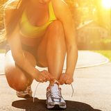 Beautiful woman in fitness wear ties shoelaces Royalty Free Stock Images