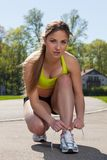 Beautiful woman in fitness wear ties shoelaces Stock Photography
