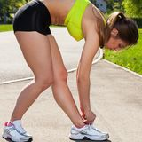 Beautiful woman in fitness wear ties shoelaces Stock Images