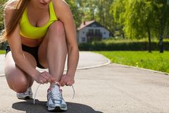 Beautiful woman in fitness wear ties shoelaces Royalty Free Stock Photos