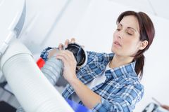Beautiful woman fixing ventilation parts. Electrician Royalty Free Stock Photo