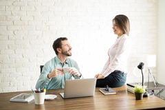 Beautiful woman flirting with a coworker Stock Images
