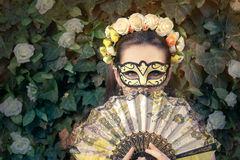 Beautiful Woman with Floral Wreath, Mask and Fan Stock Image