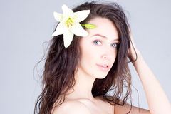 Beautiful woman with flower in curly hair. SPA treatment. Young woman with flower in curly hair. SPA treatment Royalty Free Stock Photos