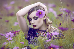 Beautiful woman in a flower field stock photography