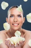 Beautiful woman with flower petals falling, close up Stock Images