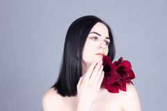 Beautiful woman with flower touches the chin Royalty Free Stock Image