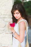 A beautiful woman with a flower in a wihite dress. At a column stock photo