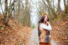 Beautiful woman with flower wreath in fur coat outdoors in the autumn park Stock Image