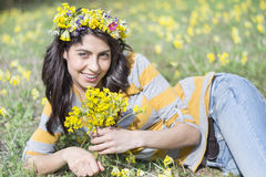 Beautiful woman with flower wreath laying in a meadow of flowers Royalty Free Stock Images