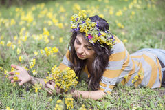 Beautiful woman with flower wreath laying in a meadow of flowers Stock Photos