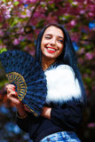 Beautiful Woman with flowers glamour white fur and black fan in hand. Stock Photos