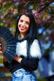 Beautiful Woman with flowers glamour white fur and black fan in hand. Stock Images