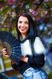 Beautiful Woman with flowers glamour white fur and black fan in hand. Stock Photo