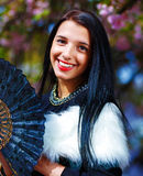 Beautiful Woman with flowers glamour white fur and black fan in hand. Royalty Free Stock Photos