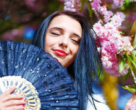 Beautiful Woman with flowers, glamour white fur Stock Photos