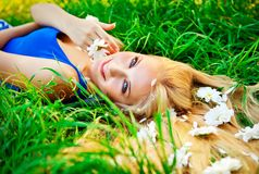 Woman lying in green grass with a flowers in hairs royalty free stock image