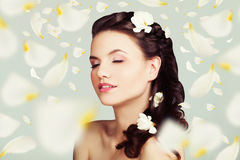 Beautiful Woman with Flowers Petals. Young Beauty Stock Photo