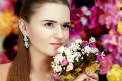 Beautiful Woman With Flowers. Beautiful pretty woman with white, pink, yellow flowers, colorful background. Attractive face straight hair professional make up Royalty Free Stock Photography