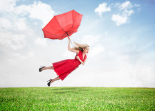 Beautiful woman flying above the grass royalty free stock photo