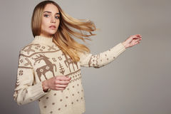 Beautiful Woman with flying hair in winter pullover. Beauty Blond Girl. Healthy hair Stock Images