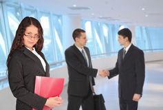 Beautiful woman with folder and businessmen Stock Image