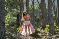 Woman dancing in a forest flicking her hair with trees in the background. stock image