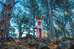 Woman in a forest with doing yoga with trees in the background. Royalty Free Stock Images
