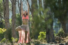 Woman doing yoga in a forest with trees in the background. Stock Photo