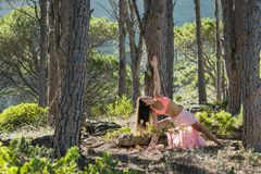 Woman doing yoga in a forest with trees in the background. Royalty Free Stock Photography