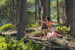 Woman doing yoga in a forest with trees in the background. Royalty Free Stock Image