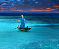 The beautiful woman in the fragile boat in a stormy sea.Portrait in a sunny day. The beautiful woman in the fragile boat in a stormy sea royalty free stock image