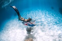 Beautiful woman freediver glides over sandy sea bottom with United States flag royalty free stock photography