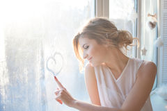 Beautiful woman with fresh daily makeup and. Romantic wavy hairstyle, sitting on the windowsill and draws on glass royalty free stock photo