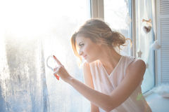 Beautiful woman with fresh daily makeup and romantic wavy hairstyle, sitting at the windowsill, draws on glass. Beautiful woman with fresh daily makeup and stock photos