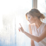 Beautiful woman with fresh daily makeup and romantic wavy hairstyle. Sitting on the windowsill and draws on glass royalty free stock image