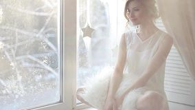 Beautiful woman with fresh daily makeup and romantic wavy hairstyle, sitting at the windowsill. Beautiful woman with fresh daily makeup and romantic wavy stock footage