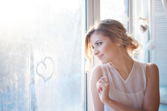 Beautiful woman with fresh daily makeup and romantic wavy hairstyle, sitting at the windowsill, draws on glass. Beautiful woman with fresh daily makeup and royalty free stock photo