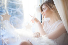 Beautiful woman with fresh daily makeup and romantic wavy hairstyle, sitting at the windowsill, draws on glass Royalty Free Stock Image