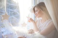 beautiful woman with fresh daily makeup and romantic wavy hairstyle, sitting at the windowsill, draws on glass stock photos