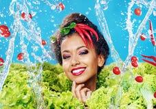 Beautiful woman among fresh vegetables Royalty Free Stock Photo