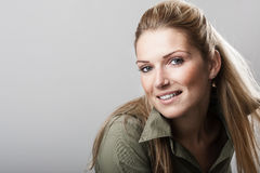 Beautiful woman with a friendly smile. Beautiful woman with long blond hair tied neatly back and a friendly smile looking at the camera, over grey with copyspace Stock Photography