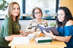 Beautiful woman with friends at book club. Portrait of attractive young hispanic women with friends reading book at a book club royalty free stock photography