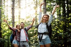 Beautiful woman and friends hiking in forest royalty free stock photography