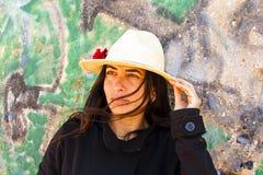 Beautiful woman in front of a graffiti brick wall Royalty Free Stock Image