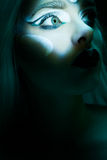 Beautiful woman with frozen makeup in dark closeup. Mesmerising eye of woman in dark scene portrait with frozen makeup looking up closeup Stock Images