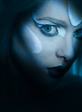 Beautiful Woman with frozen makeup in dark closeup. Mesmerising eyes of woman in dark scene portrait with frozen makeup  looking in to the camera closeup Royalty Free Stock Image